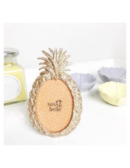 Pastatomas nuotraukų rėmelis ananaso formos pastatytas ant stalo šalia žvalių